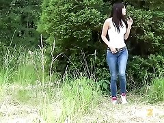 Beautiful girl squats in the grass and pees