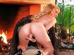 Blonde Bombshell Poses by the Fireplace